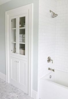 built-in linen closet, marble, subway tile with gray grout. by Hercio Dias