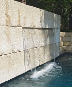 modern stone pool wall water feature and fountain using large stone slabs and a sheer descent waterfall. ohlenburg inc. swimming pool design - dallas, texas