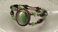 Black magnetic hematite, lime green oval pendant, silver magnetic hematite beads, lime green cat eye beads and magnetic clasps.  The pendant also