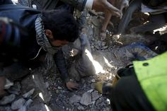 People uncover the body of a man from under the rubble of a house destroyed by an air strike near Sanaa Airport, Yemen, March 26, 2015. Saudi Arabia and Gulf region allies launched military operations including air strikes in Yemen on Thursday, officials said, to counter Iran-allied forces besieging the southern city of Aden where the U.S.-backed Yemeni president had taken refuge. REUTERS/Khaled Abdullah
