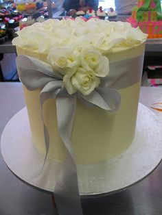 tall single tier white chocolate ganache wedding cake with silver ribbon by Charlys Bakery