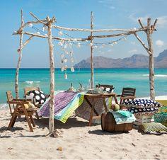 An einem Strand stehen Stühle und FALHOLMEN Tisch für draußen graunbraun lasiert, darauf eine bunte Tischdecke mit Batikmuster