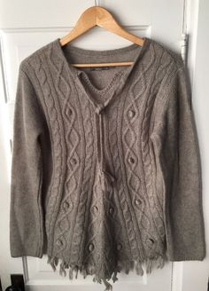 "The prAna Shelby Poncho turns a wool blend sweater into something new and fun with ties at a split neck, a fringe front and back hem and a poncho silhouette. Size medium. Length: 27"". Shoulder to shoulder: 18"". 