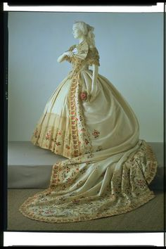 c. 1860-65. Although presentations at court took place during the day, the arms and shoulders were bare as in evening dress. In addition to a skirt worn over a very large crinoline, a train extending for several metres was an essential feature of court dress. Young debutantes would spend hours practising how to curtsey and walk backward in such an elaborate ensemble before their first presentation at court.