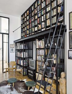 Tour an Elle Decoration Editor's Art-Filled Home Office // library, libraries, library ladder, cowhide rug, small green stools, architecture, books