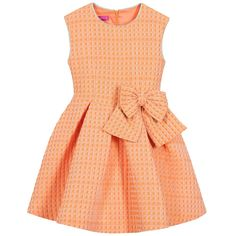 Girls orange quilted dress from ValMax. The fabric has a raised and softly textured feel, with a geometric square patterns. The fitted bodice is sleeveless and has a large bow at the front, with a full and pleated skirt that is flared and fastens at the back with a concealed zip. It is lined in smooth cotton for comfort.