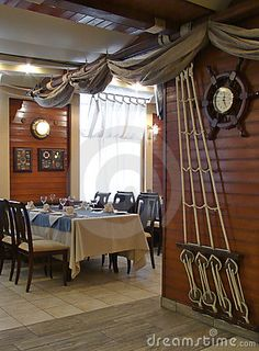 Nautical decor: ship's rigging & sails decorate the wall & ceiling in this dining area.