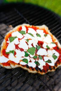 Grilled pizzas are a simple way to create the illusion of a brick oven pizza. Simply grill the pizza dough on your charcoal grill outside or indoors on a skillet right on top your stove. Tomato sauce, basil, and fresh mozzarella represent the colors of the Italian flag.