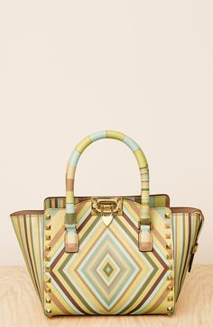A diamond pattern framed by gleaming pyramid studs takes graphic impact to the edge on this structured shopper from Valentino for a retro vibe.