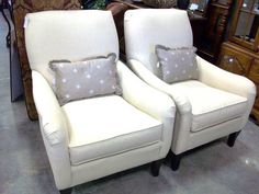 Matching pair of chairs in cream colored linen-like fabric by Sam Moore.