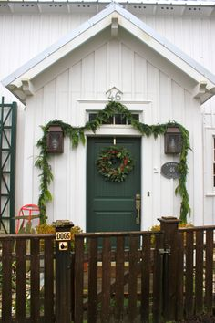 White, dark green door, beach house, exterior paint and trim ideas, garland, Christmas, sled decor, cute porch light