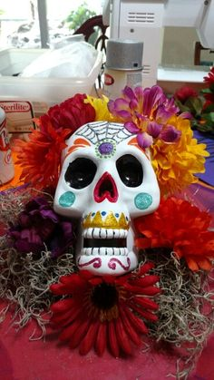 Day of the dead center piece created almost exclusively from dollar tree items. The skull, tray, moss, flowers, and foam all came from dollar tree.
