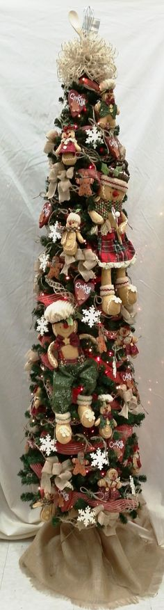 This beautiful tree showcases adorable Gingerbread men and is finished off with a kitchen utensil and burlap bow topper! Primitive Christmas Tree, Gingerbread Christmas Tree, Country Christmas Trees, Gingerbread Decorations, Christmas Tree Themes, Noel Christmas, Holiday Tree, Rustic Christmas, Gingerbread Men