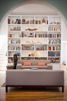 An eclectic floor-to-ceiling bookshelf acts as this room's accent wall — it's a bold way to show off your most prized knick-knacks (and books, of course). Click through for more living room decor ideas.