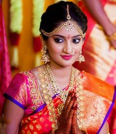 South Indian bride in gold and gemstone jumkas, long chain, necklace, matha patti and nose ring