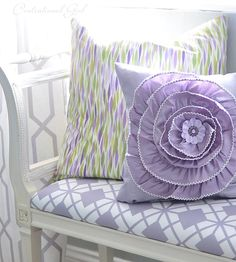 lavender flower pillow and the green and lavender/lilac pillow behind it.  These would be adorable in my bedroom.