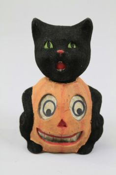ANTIQUE BLACK CAT/PUMPKIN HALLOWEEN CANDY CONTAINER  A Halloween pumpkin jack-o-lantern with paper face and the head of a black cat with black flocking covering its head, arms and tail, the cat's head separates from the pumpkin body.