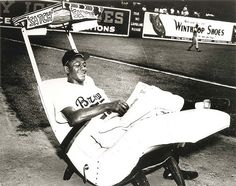 """Satchel Paige in his rocking chair, ca. 1952    St. Louis Browns pitcher Leroy """"Satchel"""" Paige relaxing in his bullpen rocking chair during a game. Photograph, ca. 1952. Missouri History Museum Photographs and Prints. Sports. N22475."""