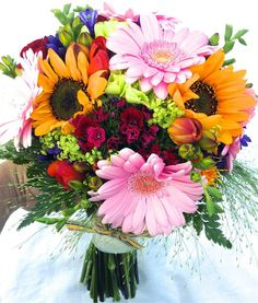 Colour packed hand-tied bridal bouquet featuring pink gerberas, red Sweet William, orange freesias, blue agapanthus, sunflowers and fountain grass, designed and made in the UK by Sophie Townsend Flowers, sophietownsend.com