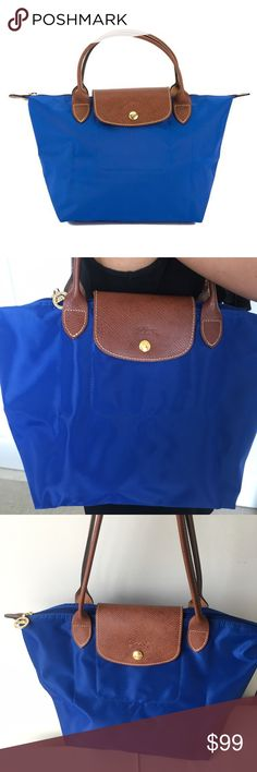 NWOT Authentic Longchamp Le Pliage blue handbag Brand new without the tag! Longchamp Le Pliage collection combines heavy nylon with tan grained leather trim in classically cool styles. A necessary basic the totes and backpacks fold/unfold for extra use. Zipper tops and goldtone hardware. This style tote comes in 4 sizes: small medium large and extra large. 8.25 in. X 8.25 in. X 5.5 in. / Strap Drop = 3 in. Longchamp Bags