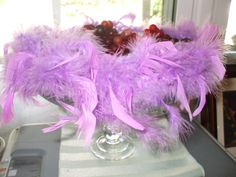 Old ceiling light globe painted silver, glue to glass candlestick, glue purple boa to top of glass light globe, fill with grapes
