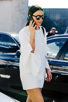 Having a little white dress is just as important as having a little black dress. We love how this street style babe daintily styles her white dress with fluttering tie-sleeve with a simple low ponytail, black mirrored sunglasses and minimal rings.