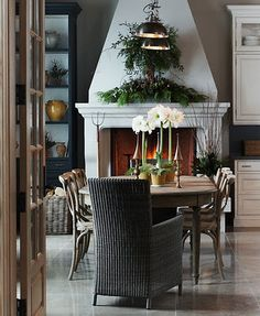 michael graydon's rustic dining room with wicker host chair and green holiday garland over a large white fireplace Dining Room Fireplace, White Fireplace, Dining Rooms, Dining Table, Kitchen Fireplaces, White Mantle, Fireplace Mantel, Fireplace Design, Dining Area