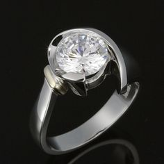 Semi bezel semi tension brilliant cut diamond solitaire ring.  Dramatic sculpted lines cradle a solitaire 2.00 carat diamond as you've never seen before.  Designed as wearable art, not cookie cutter jewellery.