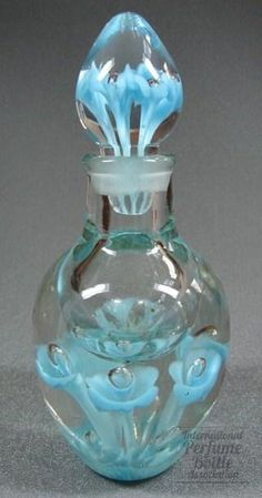 "Paperweight Perfume | International Perfume Bottle Association Perfume Bottle Material(s): glass Designer/Maker: St Clair Glass Origin: Elwood, Indiana Label: paper label on base Date or Era: 1960s Dimensions: 7.25"" H Additional Information: A paperweight perfume bottle, clear with sky flowers and air bubbles in both the bottle and matching stopper. This is an early example of American studio glass."