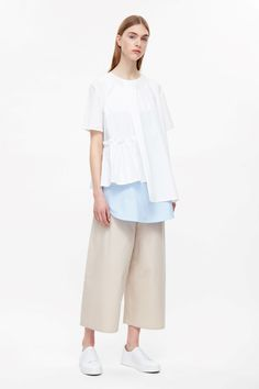 Designed with a frill detailed hemline and an overlapping front panel, this top…