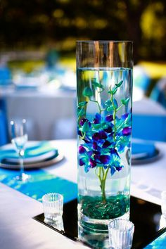 Blue orchids submerged in water as centerpieces. Simple, but so pretty. This would look great in a peacock themed wedding with peacock feathers sticking out the top of the center piece :)