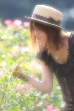A woman in a bright rose garden.