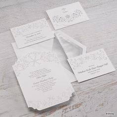 A love for winter's beauty and for fairy tales combine on this bright white wedding invitation with icy swirls and sparkling foil snowflakes framing your wording in silver and translucent glitter foil.