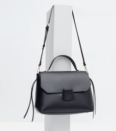 Medium black bag. Side band detail. Handle and adjustable and detachable shoulder strap. Contrasting lining with pocket. Magnetic fastening.  Height x Width x Depth: 26 x 35 x 14 cm.