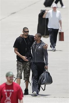 San Antonio Spurs' Tim Duncan, left, walks with teammate Gary Neal, right, as the team returns home after losing to the Miami Heat in the NBA Finals, Friday, June 21, 2013, in San Antonio. At rear is head coach Gregg Popovich.