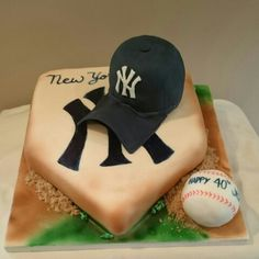 """New york yankees cake for a 40th birthday party. The cake base is finished in fondant, airbrushed, and decorated with """"grass"""" and """"dirt"""". The Yankees symbol is hand painted. Home plate and the cap are hand carved cakes. The baseball is a big cake ball. As always, everything is edible and delicious!"""