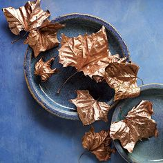 Metallic Painted Leaves:A smattering of leaves can make a pretty centerpiece when grouped together. Or, place one at each place setting for an unusual accent. Here, we sprayed thick mature sycamore leaves with copper paint.