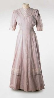 This wedding dress was worn by Minnie Beatrice Long for her marriage to a railway worker in September 1910. The wedding took place at St Andrews Church, Leytonstone. The full length dress of lilac plain weave cotton was made for Minnie by a local dressmaker. It is made in the fashion of 1910, a long 'princess' line dress with an elegant flared skirt and elaborate details created by rows of pintucks. Machine-made lace is used for decoration. Hand-made lace was expensive and exclusive and new…