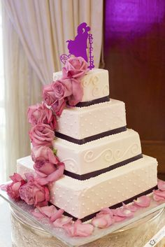 Gorgeous four-tiered wedding cake with real pink roses and a silhouette cake topper