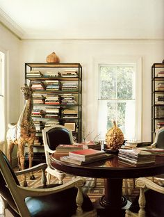 Wow, a dining room with bookshelves and books!  Be still my heart. Love the giraffe.