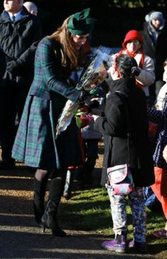 Britain's Duchess of Cambridge receives flowers and talks to people after she and other members of the royal family attended a Christmas Day Service 2013 at St. Mary's church