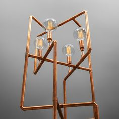 Sculpturelike floor lamp made of copper and glass pipes. Here shown with large, Edison light globes.