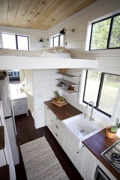 The interior is finished with white shiplap walls, chocolate birch hand scraped flooring, and a natural wood ceiling.