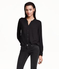 V-neck blouse in woven crêpe fabric. Shoulder tabs, chest pockets, and long sleeves with roll-up tab and button. Rounded hem, slightly longer at back.