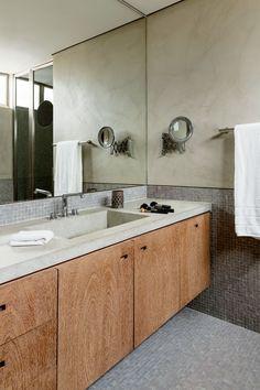 Um dos banheiros da suíte é composto por freijó lavado, limestone cinza e pastilhas grafite, da Vidrotil