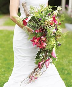 """Brides.com: Wedding Flower Bouquet Shapes. Waterfall. A bountiful mass of flowers at the top of the bouquet slowly tapers downward—definitely a candidate for """"most dramatic."""" Here the flowers and greenery are arranged on a piece of driftwood to help achieve a teardrop shape.  Bouquet of orchids, mini ferns, stars of Bethlehem, tweedia, begonia leaves, calla lilies, sweet peas, succulents, and brunia by Steven Bruce Design"""