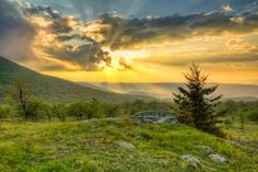 Sunbeams explode from behind passing clouds during sunset as seen from White Top Mountain Virginia