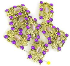 *Cast in bright gold with a beautiful ornate design and loaded with stones. The center is purplish fiber optic stone made of smooth lucite. The outer stones are light amethyst in color. This is a fair