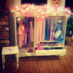 Finished princess dress up closet made out of an old entertainment center and matching bedside table. Diy