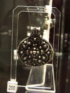 Zawieszka kolista; srebro, X-XI w., dł. 4,4 cm, wymiary tarczki 3,2 x 3,8 cm, Obra Nowa.